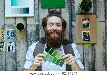 Happy bearded man with green color swatches lying on the floor