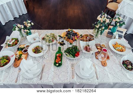 Table setting. Table served for wedding banquet. White napkin on a white empty plate on a dining table