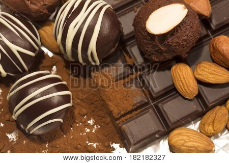 Chocolate truffles with almonds on a chocolate bar