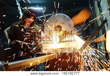 girl in a theatrical mask on the machine cuts a metal pipe.sparks fly