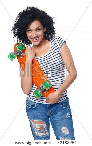 Happy smiling mixed race african american - caucasian female in distressed jeans with skateboard