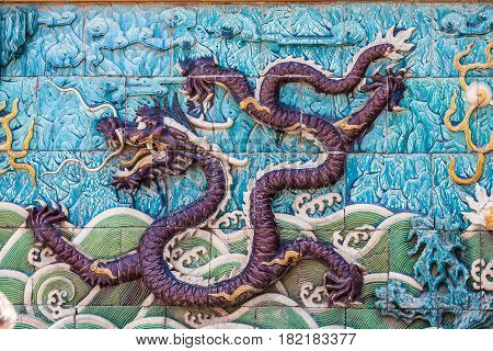 Furious purple dragon with green waves and blue clouds made from glazed tiles on the nine dragon wall in the Forbidden city in Beijing