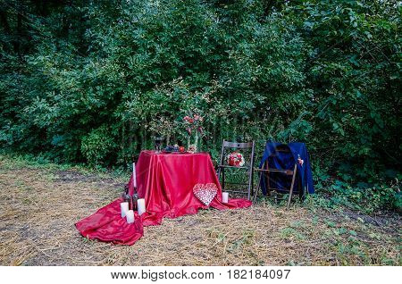 Wedding decorations outdoors. Glasses of wine plate with fruits and floral decorations on the table. Decorated table with a burgundy tablecloth for a romantic dinner. Bottles with wax drops and white candles on a tablecloth. Heart made of wine cork. Two c