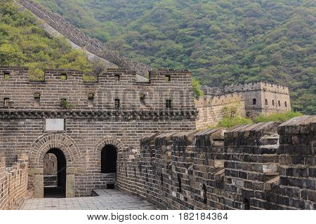 Entrance to watchtower of the Great Wall of China on the Mutianyu section with scenic mountain slope on the background
