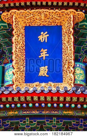 Vertical blue inscribed board in golden frame adorned carved floral ornaments with dragons on chinese Temple of Heaven