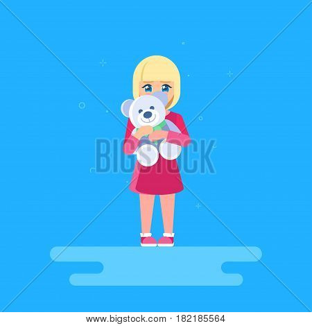 The girl is hugging a teddy bear. She is standing at full length and hiding behind a toy. The shy child.