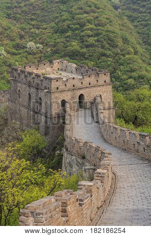 The Great Wall of China watchtower with arched windows and viewing platform against mountain hill covered forest