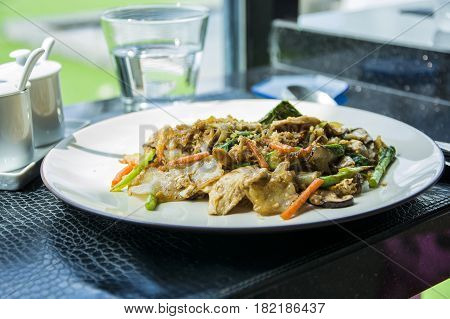 Close up shot of freshly made Thai dish with chicken served on white plate.