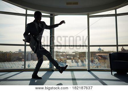 Energetic businessman with briefcase dancing indoors