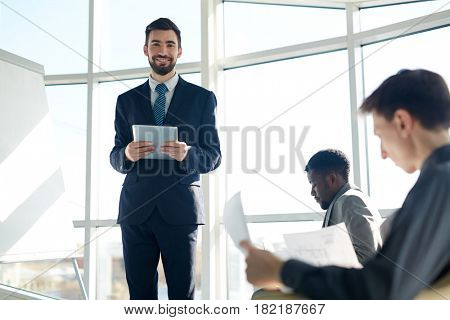 Young man with touchpad standing by whiteboard during business seminar