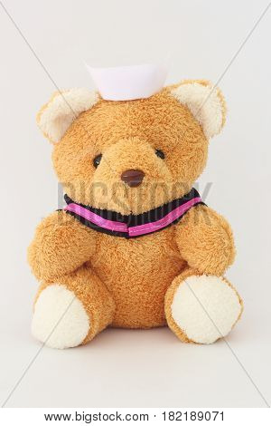 Teddy bear wearing a nurse hat on a white background.