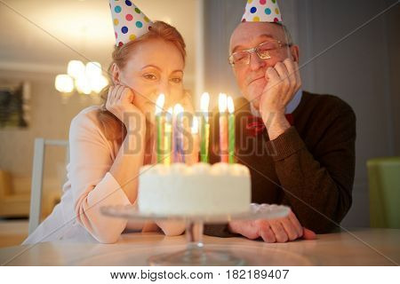 Happy spouses looking at burning candles on birthday cake