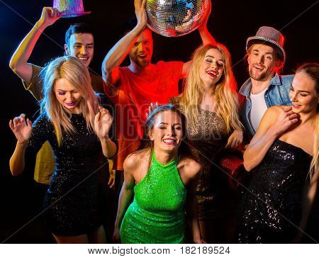 Dance party with group people dancing . Women and men have fun in night club. Happy girl in green evening dress on foreground and disco ball on background.