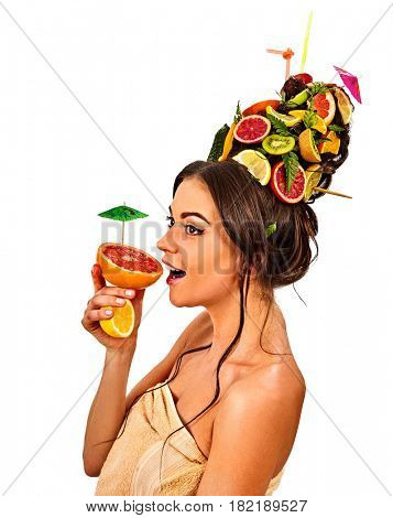 Hair mask from fresh fruits on woman head. Girl with hairstyle and bare back hold halves of orange with cocktail umbrella for organic skin and body therapy. Concept of healthy and beauty on isolated.