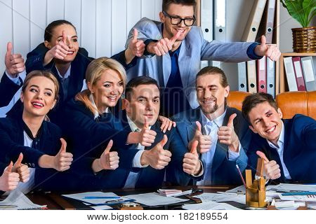 Business people office life of team people are happy with thumb up sitting table . Cabinets with folders in the background.