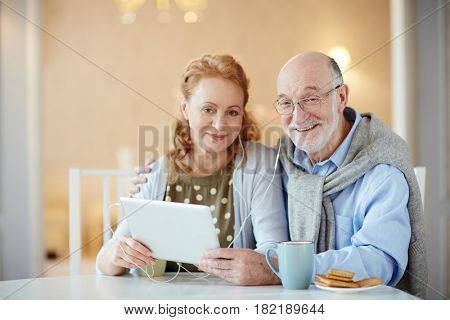 Happy mature couple with touchpad and earphones watching video