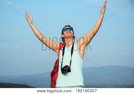 Happy handsome man photographer with camera or traveler smiling with hands gesture raised to blue sky in stylish fashionable sunglasses and cap on sunny summer day. Photography and hobby