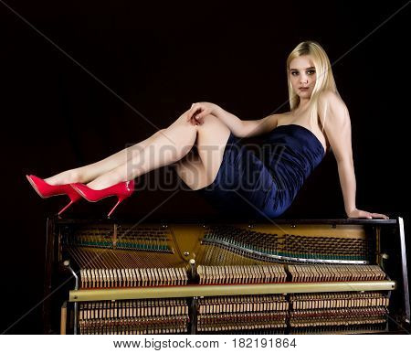 fashion young woman lies on old retro wooden piano with keyboard and posing.