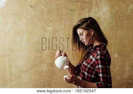 pretty woman with stylish blond long hair in red plaid shirt and blue jeans holding white ceramic tea pot teapot on beige wall. Teatime and ceremony
