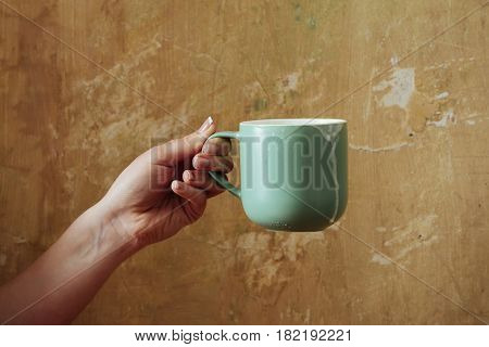 female hand with blue cup with kefir butter milk yogurt or turkish drink ayran natural dairy product on beige wall background. Dieting and healthy eating