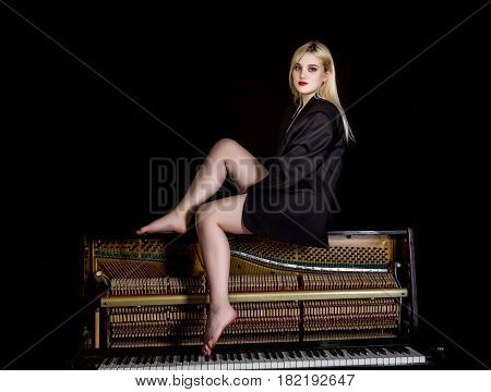fashion young woman in a man's jacket, sitting on old retro wooden piano with keyboard and posing.