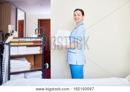 Concierge with clean towels standing by wall of hotel-room