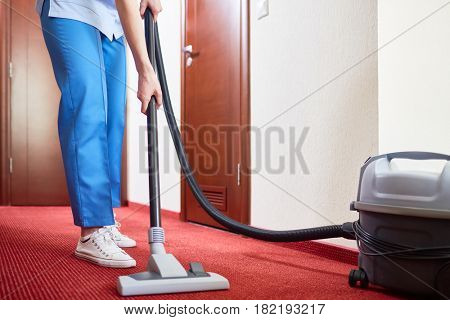 Housekeeper cleaning carpet with vacuum-cleaner
