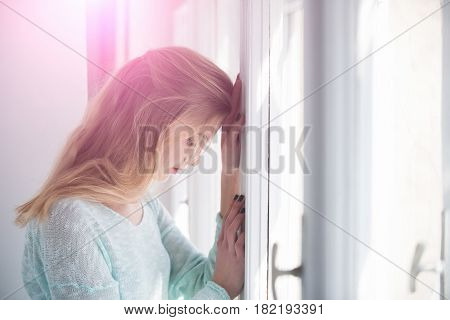 Pretty girl or young woman with blond long hair and cute face leaned against window frame on sunny day. Future perspective and outlook