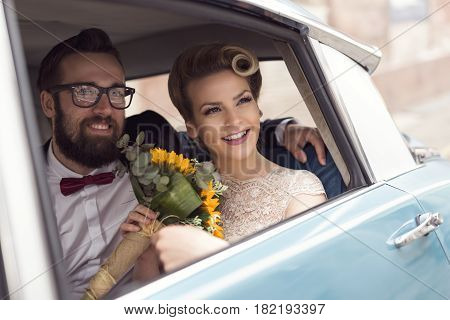 Young newlywed couple sitting in a retro vintage car hugging and going away on a honeymoon
