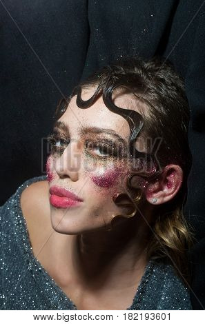 Pretty girl or sexy woman with holiday glitter makeup sparkling eye shadow rosy lips make up and cute curly lock hair fashion hairstyle on young face on black background