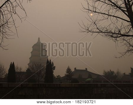 Xi'an China - Dec 23 2013: Xi'an's Landmark Big Wild-Goose Pagoda covered by heavy smog under a faintly shining sun air quality index was at the maximum of 500 points which means the air is poisonous. The smog was caused by pollution over years of industr