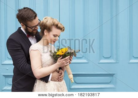 Newlywed couple hugging and standing next to a bright blue wooden door. Retro wedding concept