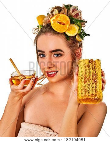 Honey facial mask with fresh fruits for hair and skin on blond woman head. Girl with beautiful face hold honeycombs for homemade organic skin and hair therapy.