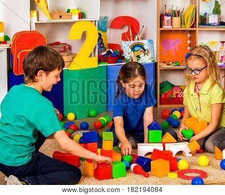 Children playing in kids cubes indoor. Lesson in primary school. Two girl and boy together play. Kindergarten kids sit on soft carpeton floor . Puzzle on background.