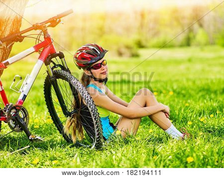 Girl traveling bicycle in summer park. Bicyclist has rest near bike. Cycling is good for health in summer and spring.