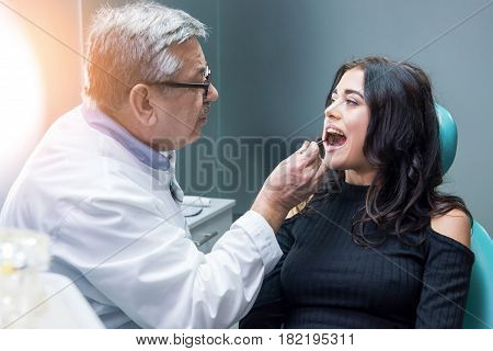 Dentist examining female patient. Stomatologist at the workplace. Highly qualified doctor.