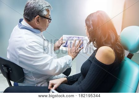 Dentist holding xray and patient. Stomatologist consulting woman. Dental implants facts.