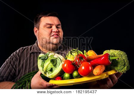 Diet fat man eating healthy food with vegetables cauliflower and sweet pepper with radish , tomatoes for overweight person. Male trying to lose weight first time .