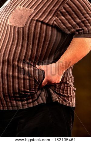 Man belly fat man holds to crease of fat on his stomach black background. Cropped shot of male body.