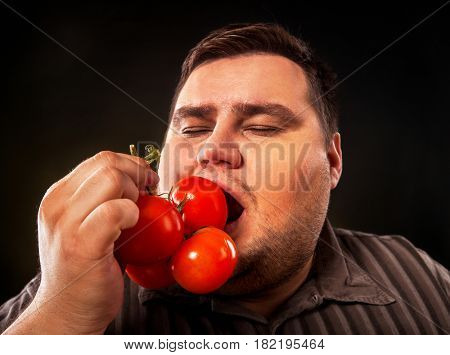 Diet fat man eating healthy food . Health breakfast with vegetables tomatoes for overweight person. Male trying to lose weight and rejoices in healthy eating.