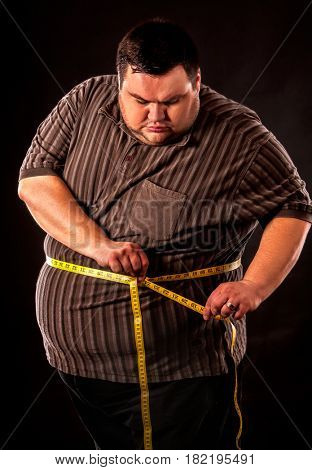 Man belly fat with tape measure weight loss around body on black background. First day of diet.
