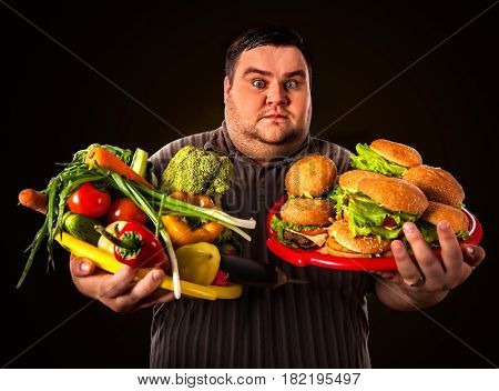 Diet fat man who makes choice between healthy and unhealthy food . Overweight male with hamburgers and vegetables trays trying to lose weight first time .