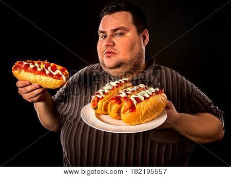 Fat man eating fast food hot dog on plate. Breakfast for overweight person. Junk meal leads to obesity. Person regularly overeats concept on black background.