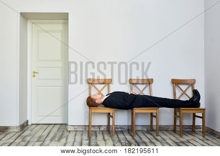 Portrait of young red haired business man bored and lying on chairs in waiting room outside office