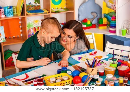 Small students girl and boy with teacher painting in art school class. Child drawing by paints on table. Mom praises son in kindergarten. Craft drawing education develops creative abilities of