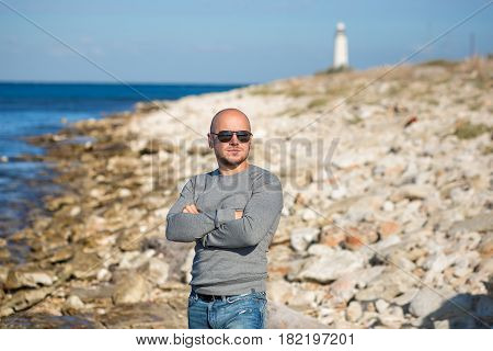 Man on a beach close to lighter beacon looking forward