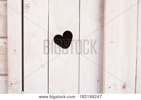 Wooden board with cut out heart shape.