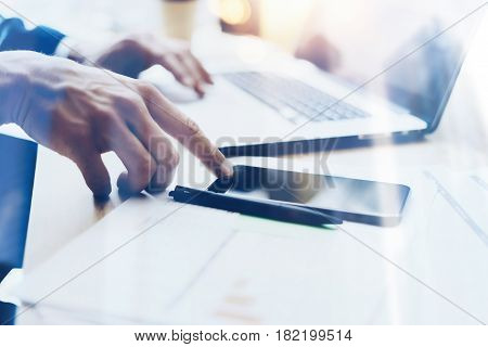 Man working on modern mobile phone at office and pointing finger to home button.Horizontal closeup view, blurred background, visual effects