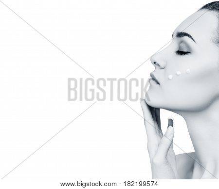 Beautiful sensual woman with cream drops on cheek. Moistening skin concept.