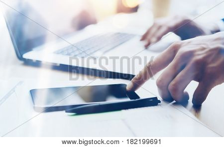 Closeup view of Man working on modern mobile phone at office and pointing finger to home button on smartphone.Horizontal, blurred background, visual effects